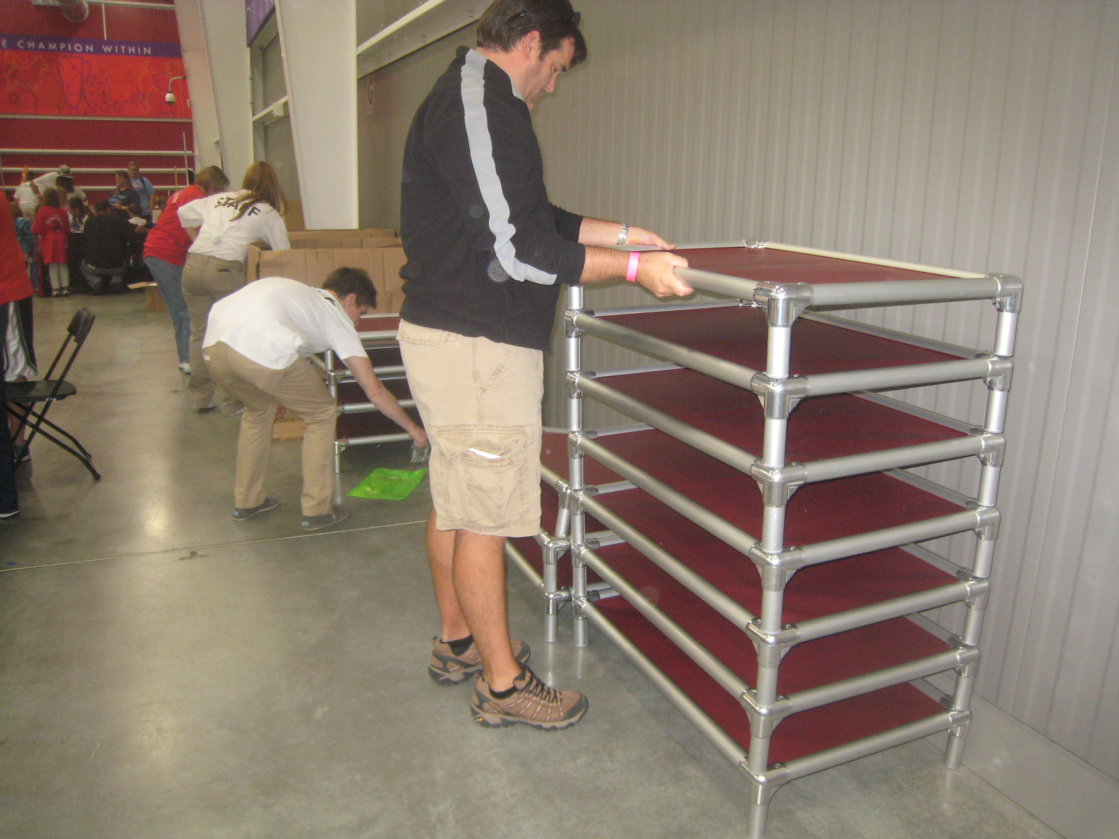 A volunteer stacks newly-assembled dog beds