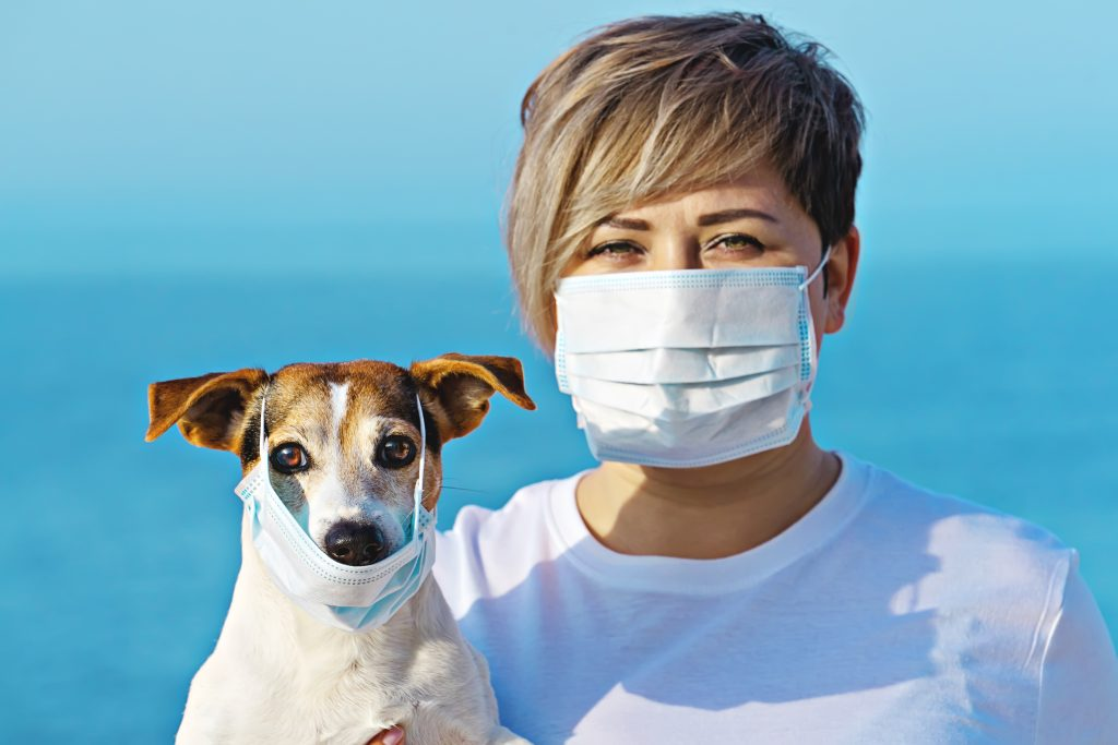 woman and dog wearing face mask